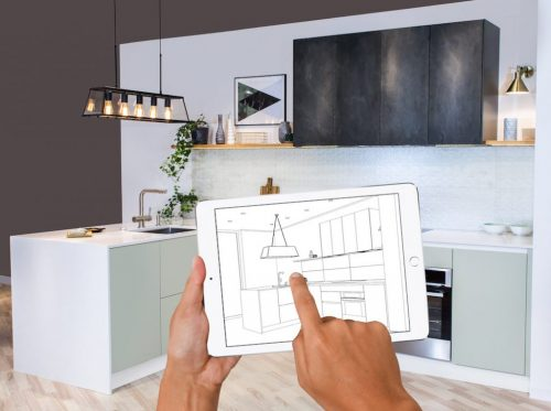 Hands holding tablet showing kitchen plans in finished room. Modern apartment. Kitchen cabinets drawing. Home Interior Design Software Programs. Project management. Construction, appliances.